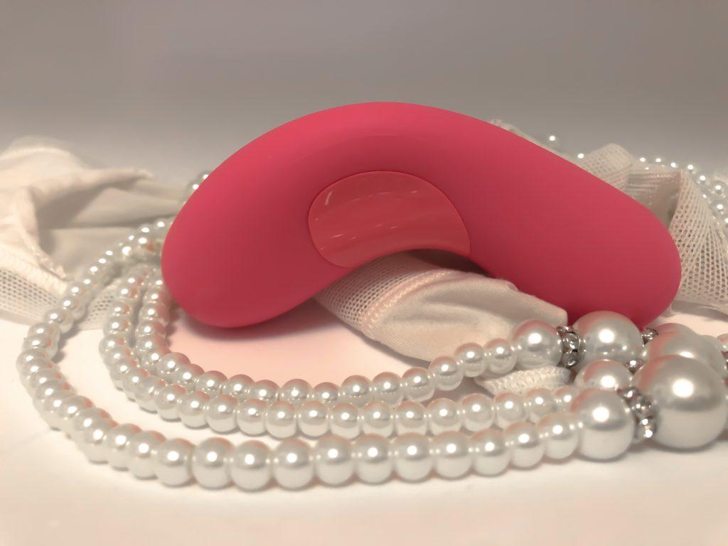 klitoris vibrator ligger ovenpå perler